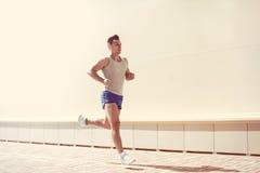 Forma fisica, allenamento, sport, concetto di stile di vita - funzionamento dello sportivo in una città Immagine Stock