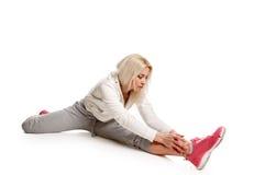 Forma fisica bionda di allenamento della donna che allunga le spaccature Fotografie Stock