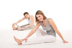 Forma fisica - coppia sana che allunga sul bianco Immagini Stock Libere da Diritti