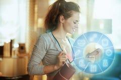 Forma fisica della donna di sport che prepara su Internet facendo uso dello smartphone fotografia stock