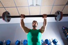 Forma fisica di allenamento dell'uomo del bilanciere alla palestra di sollevamento pesi Fotografia Stock