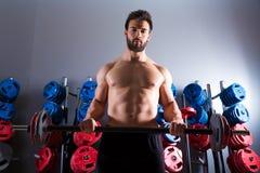 Forma fisica di allenamento dell'uomo del bilanciere alla palestra di sollevamento pesi Immagine Stock