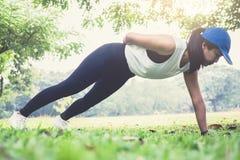 Forma fisica di allenamento di esercizio di flessione della donna che fa fuori sull'erba i Immagini Stock Libere da Diritti