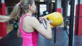 Forma fisica di Kettlebell, giovane atleta femminile che fa gli esercizi di forza nella palestra video d archivio