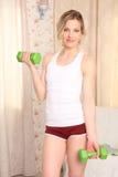 Forma fisica di pratica della giovane donna attraente sportiva, facente esercizio diritto con le teste di legno, interno della ca Fotografia Stock
