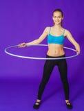 Forma fisica e concetto della palestra - giovane donna sportiva con il hula-hoop alla palestra Su una priorità bassa blu fotografie stock libere da diritti