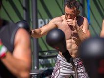Forma fisica e concetto di esercitazione: Ragazzo con il torso nudo che ha allenamento con la palla di velocità di pugilato all'a Immagini Stock
