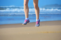 Forma fisica e funzionamento sulla spiaggia, sul corridore della donna che risolvono sulla sabbia vicino al mare, sullo stile di  Fotografia Stock