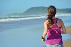 Forma fisica e funzionamento sulla spiaggia, sul corridore della donna che risolvono sulla sabbia vicino al mare, sullo stile di  Immagine Stock