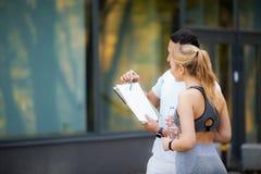 Forma fisica Esercitazione personale della donna di Takes Notes While dell'istruttore all'aperto fotografia stock libera da diritti