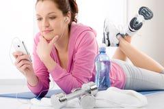 Forma fisica - la donna ascolta musica mp3 si distende fotografia stock
