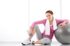 Forma fisica - la donna si distende la sfera di esercitazione della bottiglia di acqua Fotografie Stock Libere da Diritti