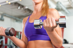 Forma fisica - la donna sta esercitandosi con il barbell in ginnastica Fotografie Stock Libere da Diritti
