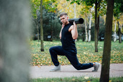 Forma fisica maschio che fa affondo di esercizio con vipr, allenamento di mattina nel parco Fotografia Stock Libera da Diritti
