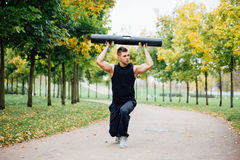 Forma fisica maschio che fa affondo di esercizio con vipr, allenamento di mattina nel parco Immagine Stock Libera da Diritti