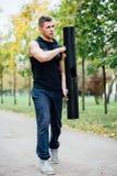 Forma fisica maschio che fa affondo di esercizio con vipr, allenamento di mattina nel parco Fotografia Stock