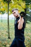Forma fisica maschio che fa affondo di esercizio con vipr, allenamento di mattina nel parco Immagini Stock