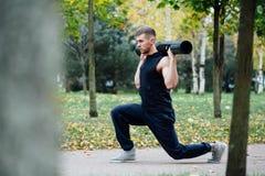 Forma fisica maschio che fa affondo di esercizio con vipr, allenamento di mattina nel parco Immagine Stock