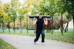 Forma fisica maschio che fa affondo di esercizio con vipr, allenamento di mattina nel parco Fotografie Stock