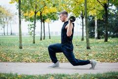 Forma fisica maschio che fa affondo di esercizio con vipr, allenamento di mattina nel parco Fotografie Stock Libere da Diritti