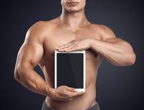 Forma fisica maschio tenendo compressa verticalmente digitale con lo schermo in bianco Fotografia Stock Libera da Diritti