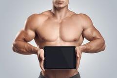 Forma fisica maschio tenendo orizzontalmente compressa digitale con scre in bianco Immagine Stock Libera da Diritti