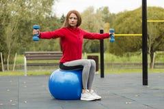 Forma fisica, sana, aerobica, allenamento, giovane donna sorridente che fa esercizio con la palla dei pilates sul campo da giuoco fotografie stock libere da diritti
