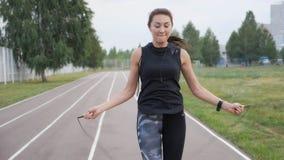 Forma fisica, sport, addestramento, parco e concetto di stile di vita - donna che si esercita con la salto-corda all'aperto video d archivio