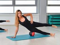 Forma fisica, sport, esercitante stile di vita - donna adatta in tuta che fa gli esercizi con palla medica alla palestra Fotografie Stock