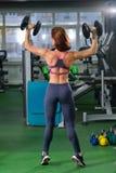 Forma fisica, sport, esercitante stile di vita - donna con le teste di legno che fanno gli esercizi in palestra, vista dalla part fotografie stock