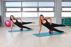 Forma fisica, sport, esercitante stile di vita - donne adatte in tuta che fa gli esercizi con palla medica alla palestra Immagine Stock Libera da Diritti