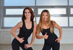 Forma fisica, sport, esercitante stile di vita - due giovani donne felici che stanno insieme vicine in una palestra e che mostran Fotografia Stock