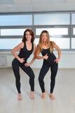 Forma fisica, sport, esercitante stile di vita - due giovani donne felici che stanno insieme vicine in una palestra e che mostran Fotografie Stock