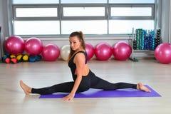 Forma fisica, sport, esercitante stile di vita - la donna invecchiata mezzo in tuta che fa le spaccature esercita la palestra immagini stock
