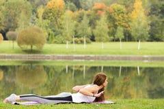 Forma fisica, sport, yoga e concetto sano di stile di vita - giovane ragazza attraente che fa asana di yoga sulla riva del fiume  Fotografia Stock