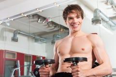 Forma fisica - uomo che si esercita con il barbell in ginnastica Immagine Stock