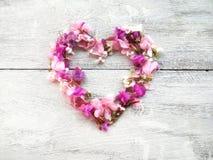 forma hermosa del corazón de las flores para la tarjeta del día de San Valentín en el fondo de madera Fotografía de archivo libre de regalías