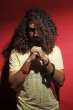 Forma nova do indivíduo e cabelo encaracolado bonito longo contra o vermelho Fotografia de Stock Royalty Free