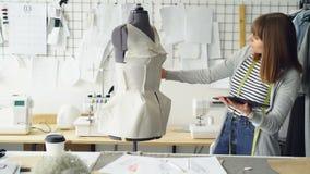 A forma nova que projeta o empresário está trabalhando com tabuleta ao verificar a roupa fixou a costurar o manequim moderno vídeos de arquivo