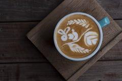 Forma piacevole del servire del caffè di arte del latte sul piatto di legno fotografia stock libera da diritti