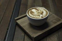 Forma piacevole del servire del caffè di arte del latte sul piatto di legno immagine stock libera da diritti