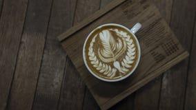 Forma piacevole del servire del caffè di arte del latte sul piatto di legno fotografie stock