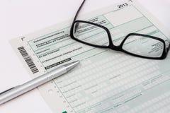 Forma podatku dochodowego powrót z piórem i szkłami fotografia stock