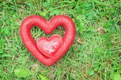 Forma roja brillante del corazón dos coloridos en la textura del césped para el fondo con el texto blanco, te amo, concepto del d foto de archivo libre de regalías