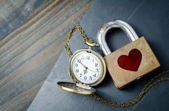Forma roja del corazón sobre el candado con el reloj de bolsillo del vintage en negro Fotos de archivo libres de regalías