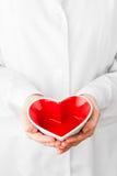 Forma roja del corazón en manos Fotos de archivo libres de regalías