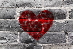 Forma roja pintada del corazón en la pared de ladrillo negra Fotografía de archivo libre de regalías