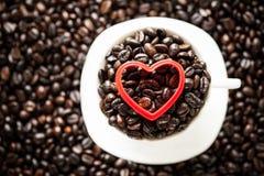 Forma vermelha do coração em feijões de café Imagens de Stock