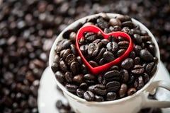 Forma vermelha do coração em feijões de café Fotos de Stock Royalty Free