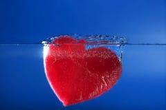 Forma vermelha do coração dos doces que afunda-se na água azul Fotografia de Stock Royalty Free